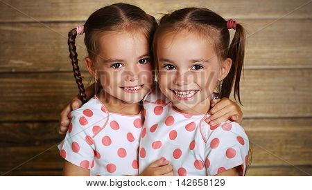happy family children twin sisters hugging and laughing