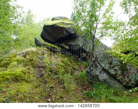 Large boulders, dolmens covered by moss. Landscape with rocks on the shore of lake Ladoga in Karelia. Northern Europe in all natural and rugged beauty.