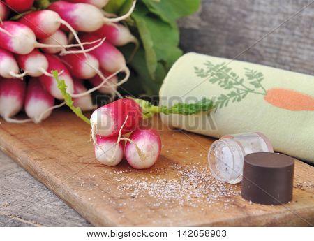 fresh radishes on board kitchen with salt