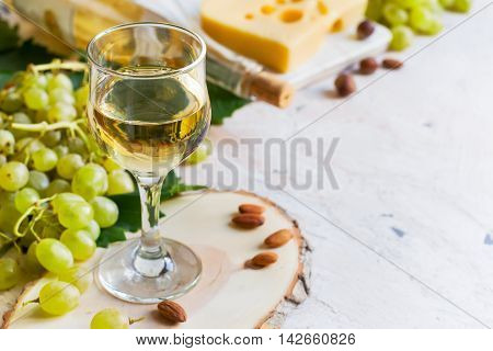 White wine in a glass on a white background copy space.