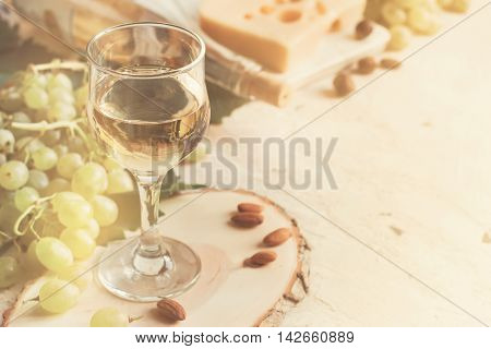 Vintage background with a glass of white wine and grapes tinted copy space