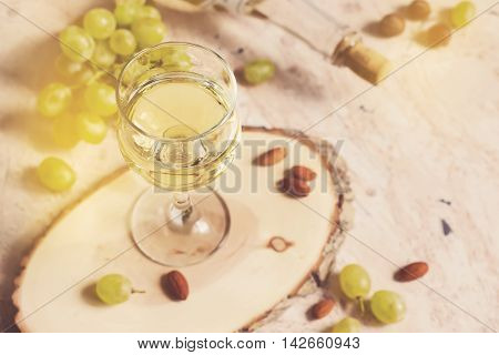 Glass of white wine on the background of grapes and nuts tinted.