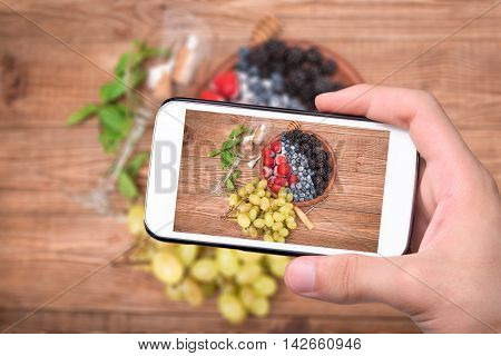 Hands taking photo white wine sangria with fresh berries with smartphone.