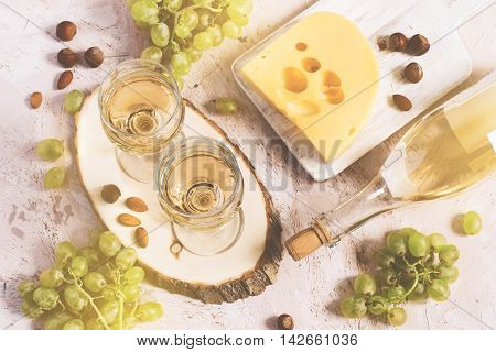 Two glasses of white wine cheese and grapes. Top view tinted.