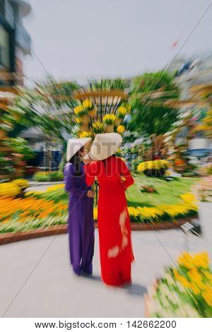 HO CHI MINH CITY VIETNAM - FEBRUARY 07: Vietnamese women in traditional Ao Dai dress pose for pictures at the New Year flower festival in Ho Chi Minh City Vietnam on February 07 2016.