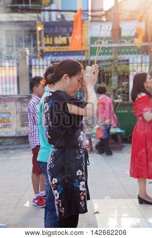 HO CHI MINH CITY VIETNAM - FEBRUARY 08: Vietnamese woman prays in the Quoc Tu Pagoda during Lunar New Year celebrations in Ho Chi Minh City Vietnam on February 08 2016.