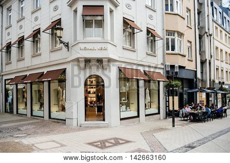 LUXEMBOURG LUXEMBOURG - JUNE 5 2016: Michael Kors luxury flagship store in the center of Luxembourg with people eating at a cafe nearby