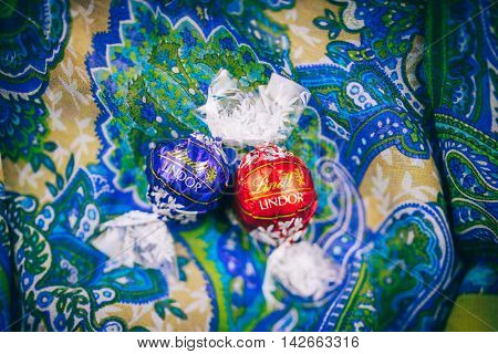 KILCHBERG SWITZERLAND - MARCH 20 2014: Two tasty Lindt Lindor chocolate truffle on a red luxury silk background.