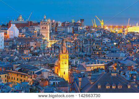 Aerial view of old town and port with cranes at night, Genoa, Italy.