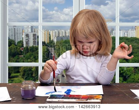 The child draws the table. Girl little blonde. Multicolored paint brush with blue. The window in the building. Outside the city the green trees panoramic view