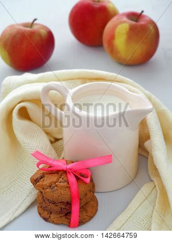 Milk Jug, Apples and Chocolate Chip Cookies on Wooden Background.
