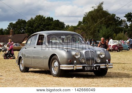 POTTEN END, UK - JULY 27: A vintage Jaguar MkII luxury sportscar exits the show arena having just given a public display at the Dacorum Steam Fair on July 27, 2014 in Potten End.