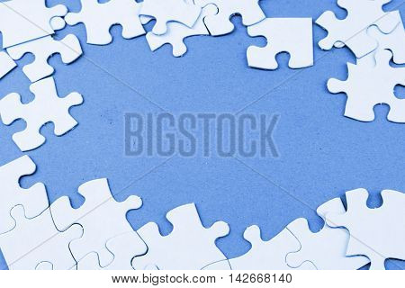 Loose jigsaw puzzle pieces on blue background