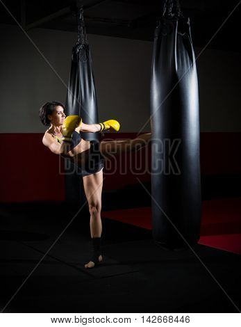 Training of kickboxer woman at sports hall