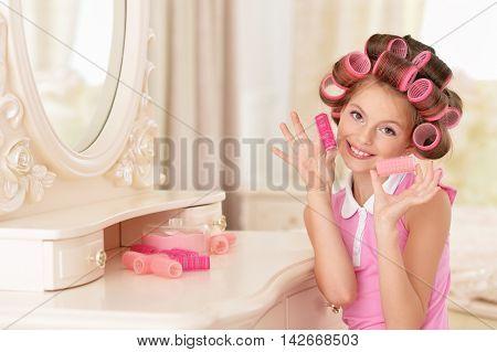 portrait of happy Little pretty girl   in hair curlers near mirror