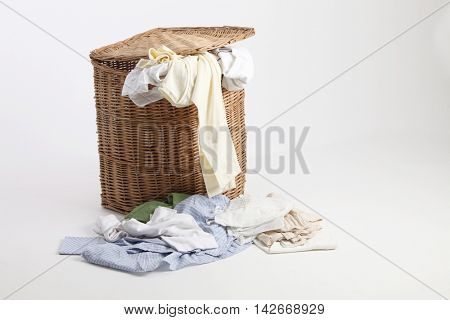 rattan laundry basket full of clothes and towels for washing