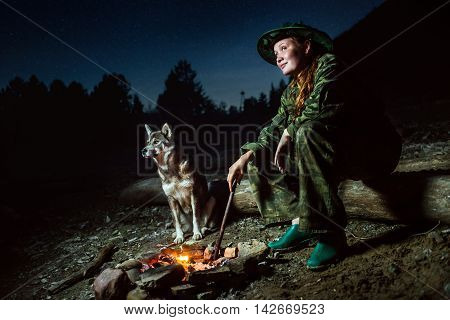 tourist girl with her dog around campfire at night moonlight with stars
