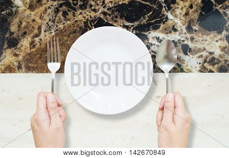 Closeup white ceramic dish on black and white marble stone table textured background in top view