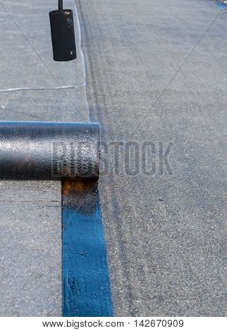 Construction workers are waterproofing a bridge surface floor at a highway. Installation of roll roofing waterproofing propane blowtorch during construction