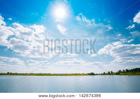 Scenic Riverine Landscape Of Skyline, River Lake Water Surface, Bright Blue Sky With White Clouds, Sun At Zenith. Copyspace Background.