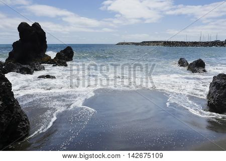 marine landscape Vila Franca atlantic ocean beach in Sao Miguel Azores island of Portugal in summer with vibrant blue sea and white waves foam on sand shore in travel destination and tourism concept