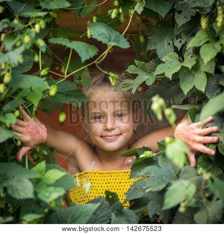 Cute little girl peeking out of the greenery portrait.