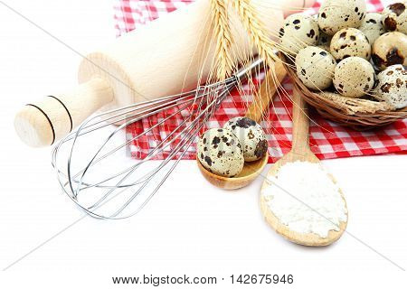 Quail eggs flour and cooking utensils on canvas isolated on white background.