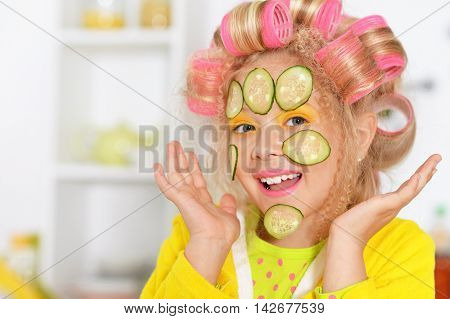 portrait of happy Little pretty girl   in hair curlers with cucumber mask