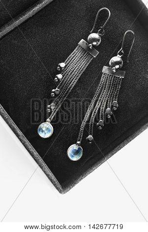 Silver earrings with blue topaz in black jewel box closeup