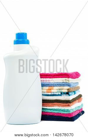 Bottle of detergent and a stack of laundry isolated on white background.