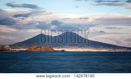 Panoramic view of the seafront of Naples in the foreground the oldest castle of the city Castel dell'Ovo and in the background the classic silhouette of the volcano Vesuvius.