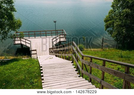 View From The Hill To Stairs Down To The Natural Wooden Boardwalk Viewing Platform Area Above The Water Next To Scenic Bank Of River, Lake Shore In Summer Spring.