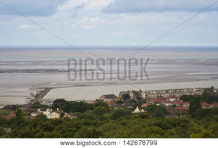 WEST KIRBY, ENGLAND, JUNE 26. Caldy Hill on June 26, 2016, overlooking West Kirby, England. Rooftops, the Marine Lake, the Tidal Flats, and the Irish Sea are seen overlooking West Kirby England.