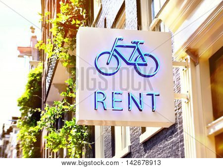 Bicycle rent sign at a shop. Sunny scene with commercial sign.