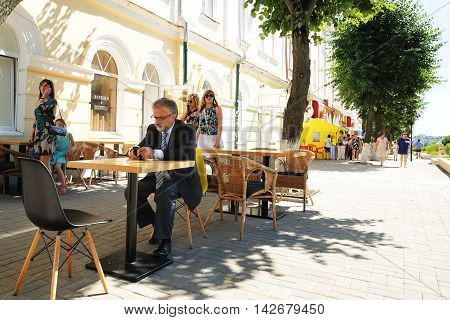 Orel Russia - August 05 2016: Orel city day. Senior lonely man sitting in outdoor cafe horizontal