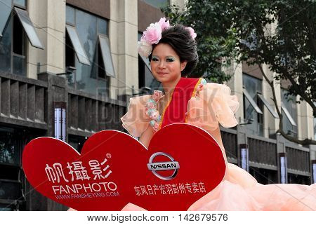 Pengzhou China - April 10 2013: Beautiful Chinese model riding in an open car on Middle Road advertising Nissan cars and Fan Photo shop