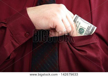 Elegantly dressed man gets out of his shirt pocket money.