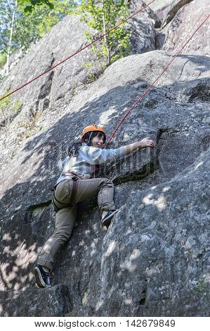 Karelia Russia - June 24 2016: pretty young woman practicing climbing on natural rocks spending so her active leisure