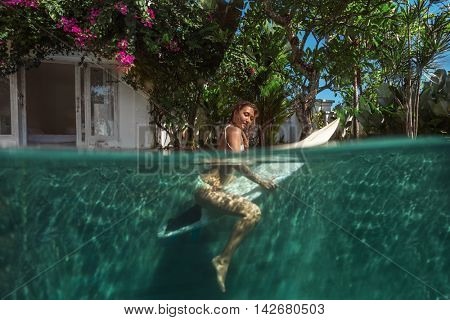 Surfer with surf board dive with fun in swimming pool