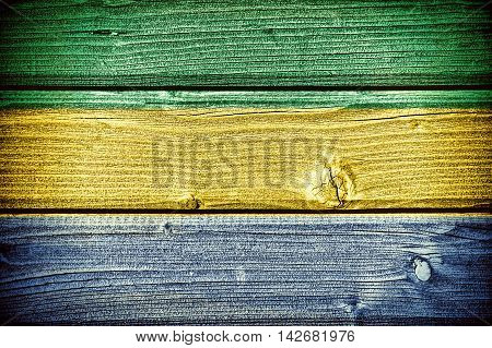 Flag of Gabon painted on old grungy wooden background: 3d illustration