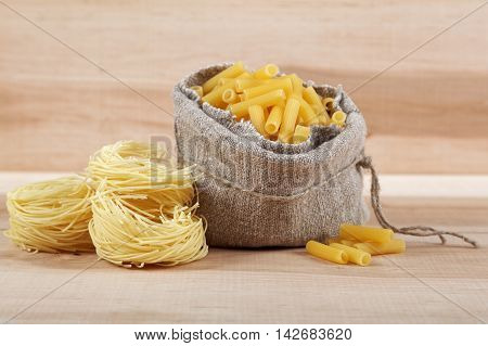 Sack with pasta on a wooden board.
