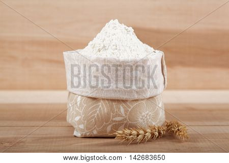Flour in a canvas bag and ear of wheat on the wooden board.