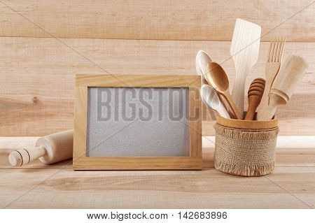 Kitchen utensils and wooden frame on a wooden board.