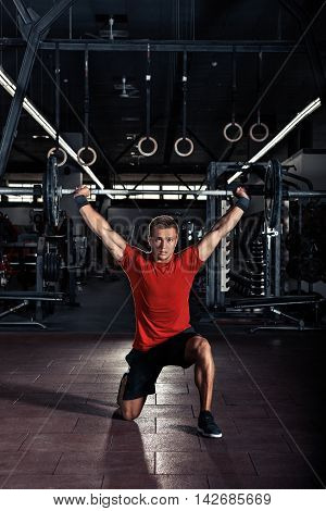 Young man with barbell flexing muscles and making shoulder press lunge in gym