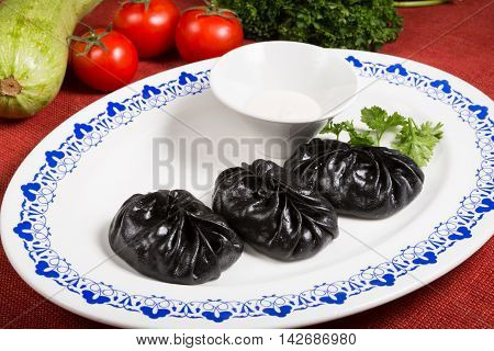 Exotic black momos served with sour cream