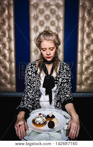 Blonde fashion girl looks at a plate of cakes Modern interpretation of Marie Antoinette