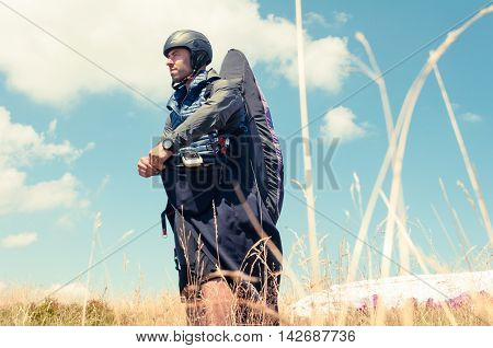 Paraglider wearing equipment ready to fly in a sunny summer day