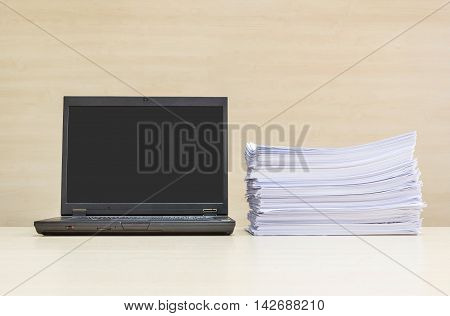Closeup black computer notebook and pile of work paper on blurred wood desk and wood wall in meeting room texture background beautiful work place interior in the office