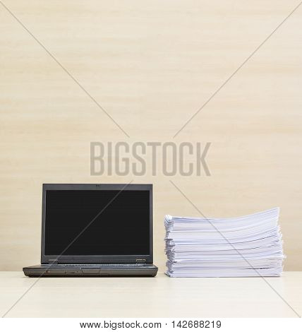 Closeup black computer notebook and pile of work paper on blurred wood desk and wood wall in meeting room texture background beautiful work place interior in the office with copy space