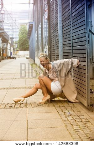 blond woman is laughing after she almost fell on the street